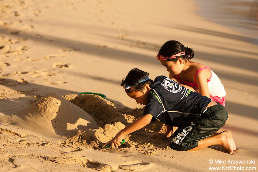 Young Asian boy & girl building a sand castle on the beach in Waikiki, Honolulu, Oahu, Hawaii