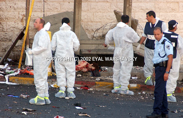 Israeli police officers stand next to a body at  the site of a suicide bombing in Jerusalem Wednesday June 19 2002. A suicide bomber exploded at a bus station wednesday killing seven and wounding 40 Photo by Eyal Warshavsky