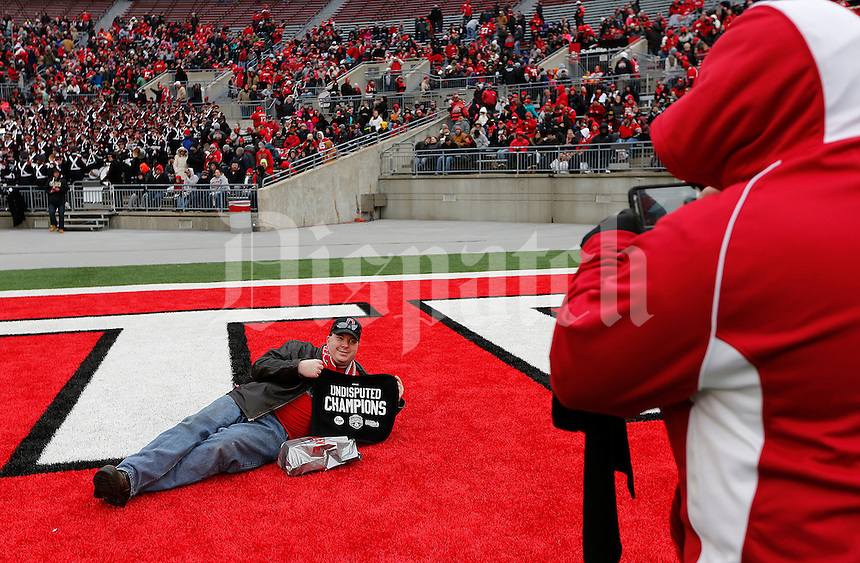 Rob Reynolds, right, of Columbus, takes a photograph of Chris Leis, of Kettering, as he poses in the end zone before the Ohio State Football National Championship Celebration at Ohio Stadium, Saturday morning, January 24, 2015. More than 40 thousand fans packed the lower stands in the stadium to celebrate the National Championship win with the football team. (The Columbus Dispatch / Eamon Queeney)