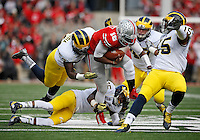 Ohio State Buckeyes quarterback J.T. Barrett (16) rumbles through Michigan Wolverine defenders, from righty, linebacker James Ross III (15), linebacker Jake Ryan (47), defensive back Dymonte Thomas (25), and defensive end Mario Ojemudia (53) during the 1st quarter of the NCAA football game at Ohio Stadium on Nov. 29, 2014. (Adam Cairns / The Columbus Dispatch)
