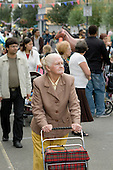 Elderly woman pushes a shopping basket in Church Street during the local Summer Festival, London.
