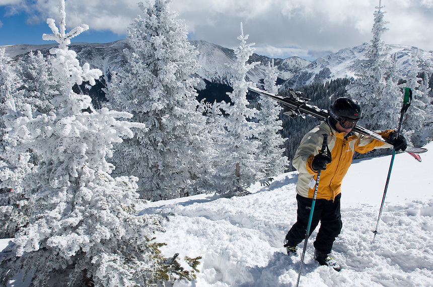 Skier Kevin Bersell, of Santa Fe, N.M., hikes through snow-covered trees to the undeveloped ridge above Taos Ski Valley, Sunday, Feb. 19, 2006. Taos, one of the nations last family-owned ski resorts, is small and intimate, and features much expert terrain. (Kevin Moloney for the New York Times)
