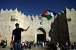 "A Palestinian protester waves his national flag during a demonstration marking the 66th anniversary of the ""Nakba,"" meaning catastrophe, when many Palestinians fled or were expelled from their towns and villages during the war of Israel's foundation in 1948, at Damascus Gate in Jerusalem's Old City May 15, 2014. An Israeli police spokesman said on Thursday that 5 Palestinian protesters were detained during the unauthorized demonstration in Jerusalem's Old City, where stones were thrown at policemen and an Israeli flag was burnt. Also on Thursday, Israeli forces shot dead two Palestinians during a stone-throwing protest marking the ""Nakba"" in the occupied West Bank. Photo by Saeed Qaq"