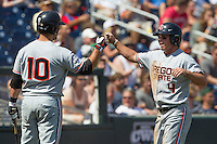 Oregon State outfielder Max Gordon (4) is greeted by teammate Dylan Davis (10) after scoring in the sixth inning of Game 11 at the 2013 Men's College World Series against the Mississippi State Bulldogs on June 21, 2013 at TD Ameritrade Park in Omaha, Nebraska. The Bulldogs defeated the Beavers 4-1, to reach the CWS Final and eliminating Oregon State from the tournament. (Andrew Woolley/Four Seam Images)