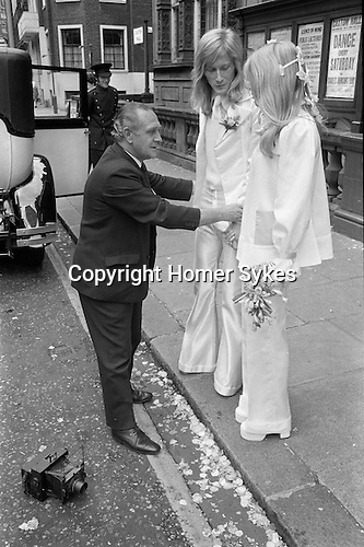 Caxton Hall Westminster London. Londons main register office until 1979. White wedding his and her uni sex clothes trouser suits flares or bell bottoms and cuban healed shoes. Long hair. 1970s fashionable London. ..He is Michael Stephens I think a well know hairdresser of the time. ..