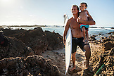 HAWAII, Oahu, North Shore, a man teaching his young son to surf in Shark's Cove in Pupukea Beach Park