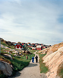 GREENLAND, Ilulissat, rear view of men walking on pathway with houses in the background