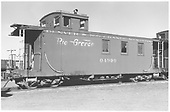 Side view of long caboose #04990 at Alamosa, flying herald, peaked roof.<br /> D&amp;RGW  Alamosa, CO  Taken by Richardson, Robert W. - 10/1950
