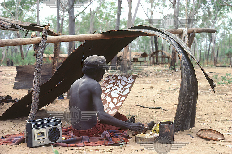 © Penny Tweedie / Panos Pictures..Aborigines, Arnhemland, AUSTRALIA..Jackie paints a bark and listens to the radio under a single bough shelter in Kalobidahdah.