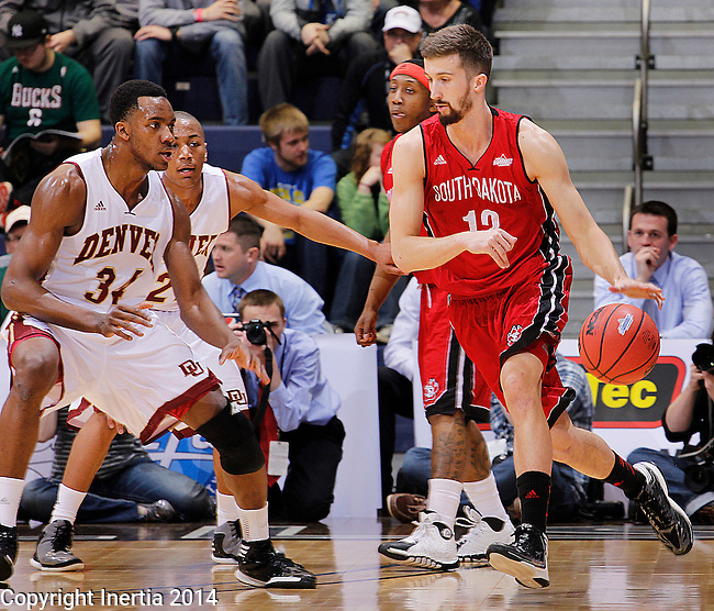 SIOUX FALLS, SD - MARCH 9:  Adam Thoseby #13 of USD dribbles toward Denver defender Chros Udofia #34 during their first round game at the 2014 Summit League Basketball Championships Sunday at the Sioux Falls Arena.  (Photo by Dick Carlson/Inertia)