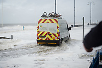Pictured: A van is caught up in water caused by waves that crash against the seaside town of Aberystwyth, Wales, UK. Saturday 21 October 2017<br /> Re: Coastal parts of the UK is facing winds of up to 70mph as Storm Brian causes roads to close and public transport to be cancelled.<br /> Roads in Aberystwyth's seafront and at nearby Aberaeron, Wales are shut on Saturday morning as a yellow &quot;be aware&quot; Met Office warning is in place.<br /> Seven flood warnings have been issued for the west Wales coast.