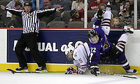 University of Nebraska Omaha's Jordan Willert works to keep control of the puck while being upended by Minnesota State University-Mankato's Kurt Davis during the second period of Friday night's game at Qwest Center Omaha. (Photo by Michelle Bishop)