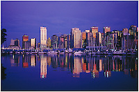Skyline of Vancouver reflecting the shimmering golden light of sunset with reflections of the buildings in the waters of Coal Harbor, taken from the seawall in Stanley Park, Vancouver, BC.