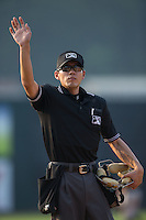 Home plate umpire Kaz Endo signals to the press box to alert them of a pitching change during the Appalachian League game between the Bristol Pirates and the Johnson City Cardinals at Howard Johnson Field at Cardinal Park on July 6, 2015 in Johnson City, Tennessee.  The Pirates defeated the Cardinals 2-0 in game one of a double-header. (Brian Westerholt/Four Seam Images)
