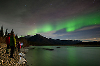 Tourist watch the aurora borealis reflect in the Koyukuk River, Brooks Range, Arctic, Alaska.