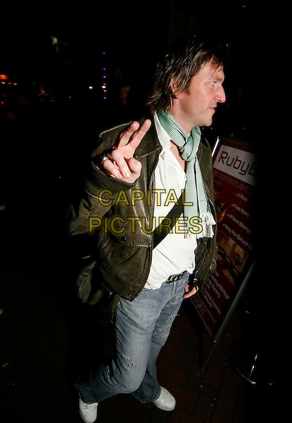LEE SHARPE.At Ruby Blue, London, UK..March 2nd, 2006.Ref: SW.full length jeans denim brown leather jacket blue scarf hand gesture peace v profile.www.capitalpictures.com.sales@capitalpictures.com.©Capital Pictures.