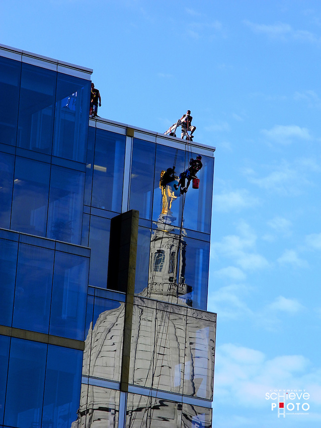 Window washers get to work on a glass building across from the Wisconsin State Capitol.