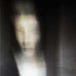 blurred image of a woman staring into the camera