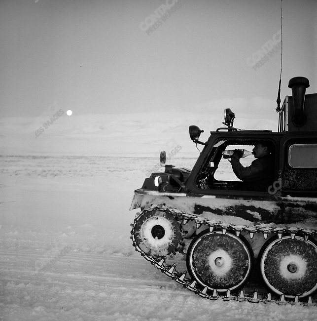 A driver of an all-terrain tracked vehicle took a break as night fell in the central part of Chukotka, on the way north from the capital Anadyr. These all-terrain vehicles are often the only form of transport in winter in Chukotka because of the extreme meteorological conditions and lack of roads bringing food, supplies and people to the distant settlements. Chukotka Autonomous Okrug, Russia, April 2007..