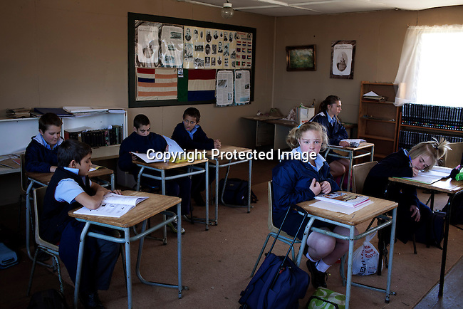 KLEINFONTEIN, SOUTH AFRICA - JULY 15: Students during a geography class in the CVO school on July 15, 2013 in Kleinfontein outside Pretoria, South Africa. The all white town with about one thousand residents are all Afrikaners with a Vortrekker heritage. Only white Afrikaners who share Afrikaner culture, language and religion are allowed to settle in the town. Their old flags and heroes are displayed on wall in the back.  (Photo by: Per-Anders Pettersson)