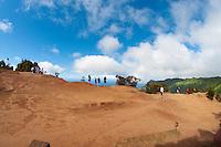 Visitors standing on the edge of Kalalau Valley's towering cliffs, Na Pali, Kauai.