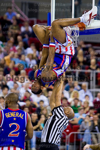 Team member of the Harlem Globetrotters basketball team performs on the basket during their exhibition match in Papp Laszlo Budapest Sports Arena.