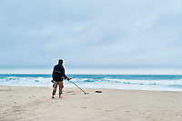 Man searching the beach with a metal detector.