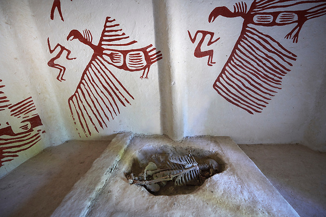 An exposed skeleton which were found in pits under the floors of some houses. On the wall are frescoes of what look like vultures, Scholars belive that dead bodies were subject to excarnation which means that their flesh was stripped from the body to leave the skeleton. A reconstruction of one of four Catalhoyuk houses to help archaeologists understand the finished structure of excavated ruins. 7500 BC to 5700 BC, Catalyhoyuk Archaeological Site, Çumra, Konya, Turkey