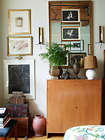In one corner of the bedroom a flea-market mirror hangs above a cabinet by Hans Wegner in the bedroom; the sconces by Tony Paul were bought on eBay, and the large black-and-white print.
