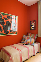 In this guest room warm ethnic stripes and deep orange walls create a cosy and welcoming ambiance
