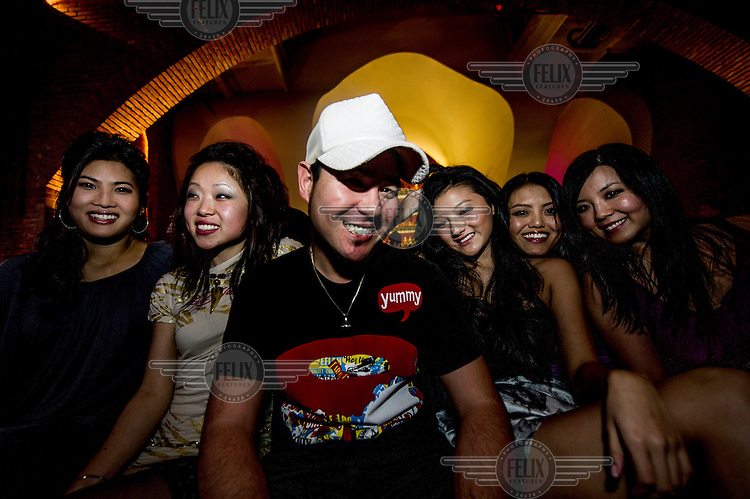 DJ Chozie with an entourage of young women at the nightclub D Lounge.