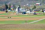 Spring overview of Oval, PA, Nippenose Valley with fields, Amishman plowing, barns and church.
