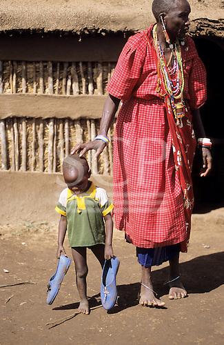 Lolgorian, Kenya. Siria Maasai Manyatta; woman and toddler, traditional beadwork earrings, blue plastic shoes.