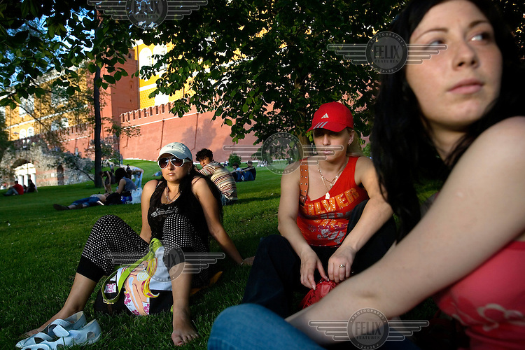 Women relax on the grass in front of the Kremlin.