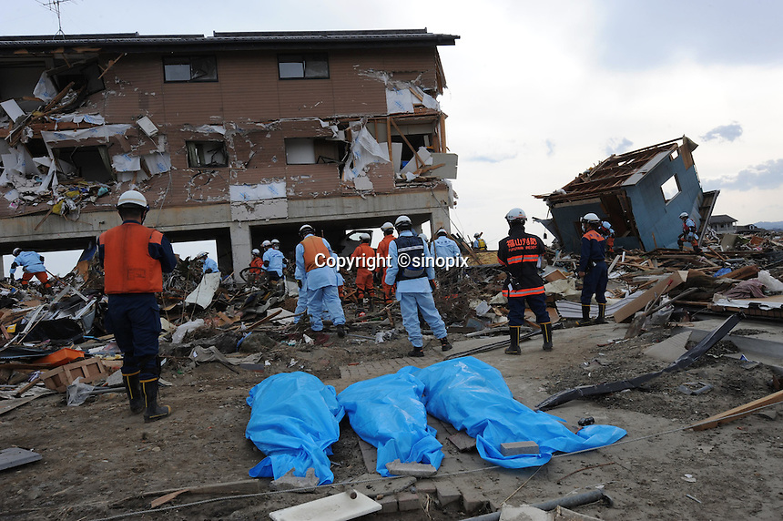 Three bodies lie in the fore-ground as a search and rescue team look through the remains of a house in the town of Natori, after the Tsunami devastated the entire pacifc coastline of Japan after the earthquake and tsunami devastated the area Sendai, Japan. One of the biggest earthquakes ever recorded struck off the coast of Japan on 11 Mar 2011 had killed thousands of people. The death toll was expected to rise dramatically, with tens of thousands reported missing..14 Mar 2011.