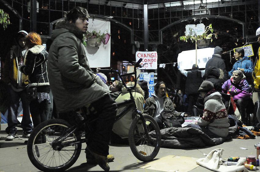 November 21, 2011, approaching midnight Occupy Toronto protesters and hundreds of supporters rally at St. James Park following a decision handed down this morning by Ontario Superior Court judge David Brown, upholding the Occupy Toronto tent camp eviction, effective 12:01, November 22, 2011.  Here an unidentified protest supporter ponders on his bike amongst other contemplative group members assembled on the band shell stage.