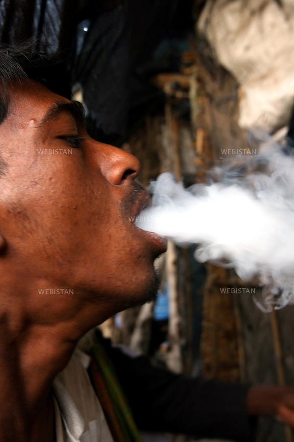 200. Bangladesh, Dhaka. Marijuana user in a slum. .Marijuana is still the most popular addictive substance in widespread use in Bangladesh but the marijuana smoked today is said to be 15 times more potent than that smoked in the 60s. The result is that those who smoke it have significantly more respiratory symptoms like chronic cough and mucus production, wheezing, and acute bronchitis, than previously..2006. Bangladesh, Dhaka. Consommateur de marijuana dans un bidonville. .La marijuana est encore la substance additive la plus populaire de grande consommation au Bangladesh, mais on dit que la marijuana fumée aujourd'hui est dix fois plus puissante que celle fumée dans les années 60. Par conséquent ceux qui la fument ont beaucoup plus de troubles respiratoire comme par exemple des toux chroniques et production de mucus, des poumons sifflant et des bronchites aigues qu'avant..