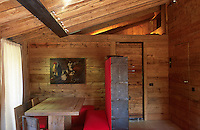 An iron cabinet made by the local blacksmith Fabbro Candeago serves as a free-standing wall between the dining area and the entrance to the chalet
