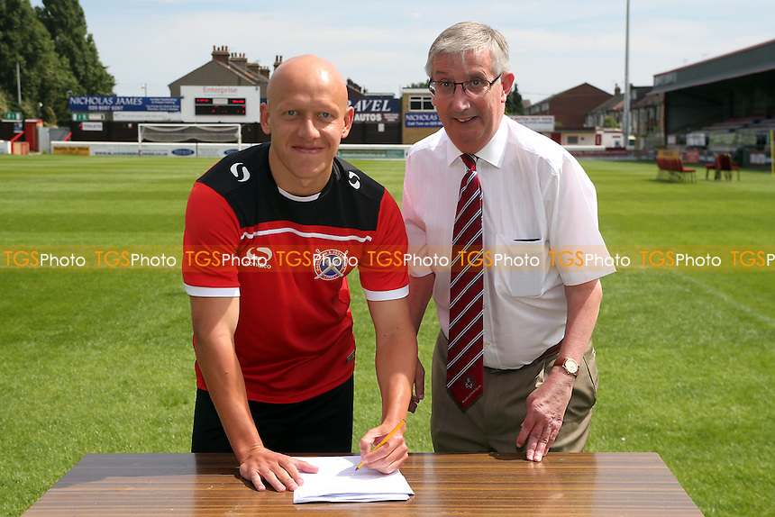Matt Richards signs for the Daggers with MD Steve Thompson witnessing the signature during Dagenham & Redbridge FC Press Day at the London Borough of Barking and Dagenham Stadium, London, England on 02/08/2015