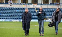 BBC Breakfast presenter Bill Turnbull walks on the pitch with film crew during the Sky Bet League 2 match between Wycombe Wanderers and Exeter City at Adams Park, High Wycombe, England on 13 February 2016. Photo by Massimo Martino.