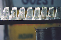 Upside-down glasses at an outdoor chai stall wait for the next customer to buy tea, India.