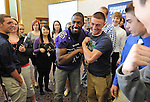 Green Bay Packers wide receiver Greg Jennings, center, flexes his muscles with Green Bay West senior Josh Ferraro after he played Financial Football with Green Bay West and Merrill High School students at Green Bay West High School on April 11, 2012. The game is designed to give students a concept about how to properly manage their money.