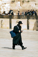 A man texting while walking in the Western Wall Plaza in Jerusalem. Romans destroyed Jerusalem and the Second Temple in 70 CE. Beginning in the 16th century, the Western Wall of the destroyed Temple became a Jewish place of pilgrimage located in a narrow alley just 12 feet wide. Immediately after the Six Day War in 1967, Israelis leveled the neighboring Arab neighborhood and created a large open area known as the Western Wall Plaza.