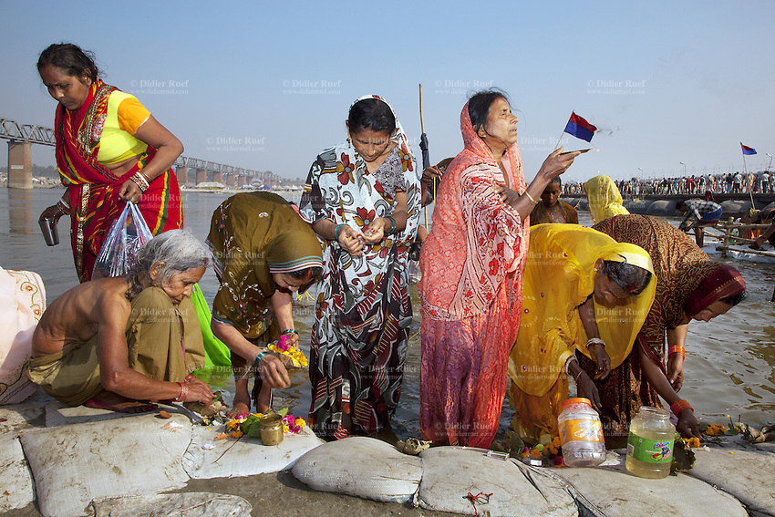 "India. Uttar Pradesh state. Allahabad. Maha Kumbh Mela. A group of Indian Hindu devotees women celebrate a puja on the banks of the river Ganges after taking a Royal bath on Mauni Amavasya Snan (Dark moon). The ritual ""Royal Bath"" is timed to match an auspicious planetary alignment, when believers say spiritual energy flows to earth. Puja (reverence, honour, adoration, or worship) is a religious ritual performed by Hindus as an offering to various deities. The Kumbh Mela, believed to be the largest religious gathering is held every 12 years on the banks of the 'Sangam'- the confluence of the holy rivers Ganga, Yamuna and the mythical Saraswati. In 2013, it is estimated that nearly 80 million devotees took a bath in the water of the holy river Ganges. The belief is that bathing and taking a holy dip will wash and free one from all the past sins, get salvation and paves the way for Moksha (meaning liberation from the cycle of Life, Death and Rebirth). Bathing in the holy waters of Ganga is believed to be most auspicious at the time of Kumbh Mela, because the water is charged with positive healing effects and enhanced with electromagnetic radiations of the Sun, Moon and Jupiter. The Maha (great) Kumbh Mela, which comes after 12 Purna Kumbh Mela, or 144 years, is always held at Allahabad. Uttar Pradesh (abbreviated U.P.) is a state located in northern India. 10.02.13 © 2013 Didier Ruef"
