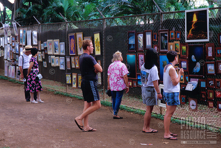 People viewing art displayed on the Honolulu Zoo fence, a weekend tradition at Kapiolani Park