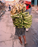PERU, Belen, South America, Latin America, rear view of boy carrying bunch of bananas at the Belen Market.