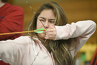 NWA Democrat-Gazette/FLIP PUTTHOFF <br /> DOWN RANGE GAZE<br /> Ashley Dominguez eyes her target Wednesday March 15 2017 during archery competition in Deb Walter's physical education class at Rogers New Tech High School. Students took part in a bull's eye contest Wednesday, but also play archery tic-tac-toe and other games, while shooting from various distances.