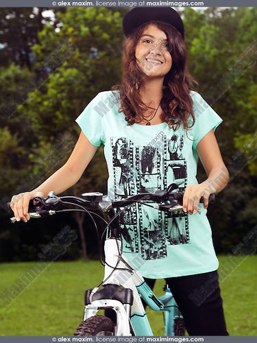 Portrait of a smiling teenage girl with a bicycle outdoors in the summer
