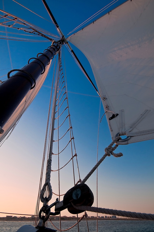 Sailboat navigates in the ocean at sunset time.