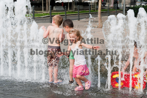 Children cool themselves down in a fountain on a public square in Budapest, Hungary on July 13, 2011. ATTILA VOLGYI